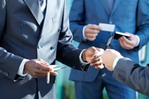 Male hand giving business card to a businessman